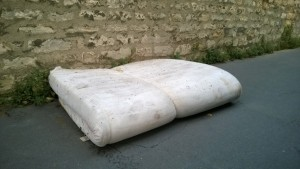 A forlorned mattress that has been abandoned in the street.