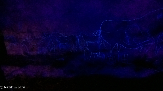Blacklight illumination of the outlines of the horses that surround the big cow.