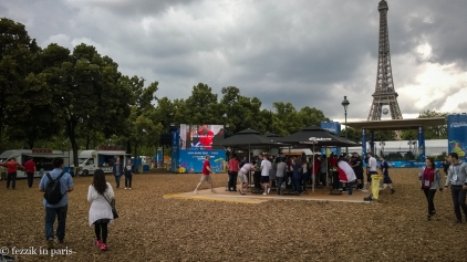 A beer tent, flanked by one of the screens scattered throughout the zone.